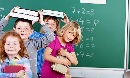Lächelnde Grundschulkinder vor Tafel