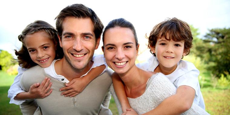 Junge Familie in der Natur blickt lächelnd in die Kamera
