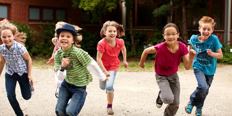 Kinder im Grundschulalter lachend und laufend auf dem Schulhof