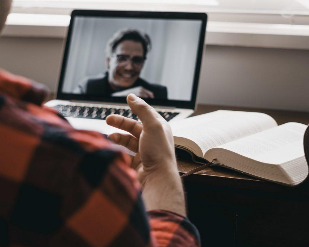 Laptop mit Chatfenster im Hintergrund auf einem Schreibtisch. Im Vordergrund sieht man einen Mann gestikulierend vor dem Bildschirm sitzend in den Chat vertieft